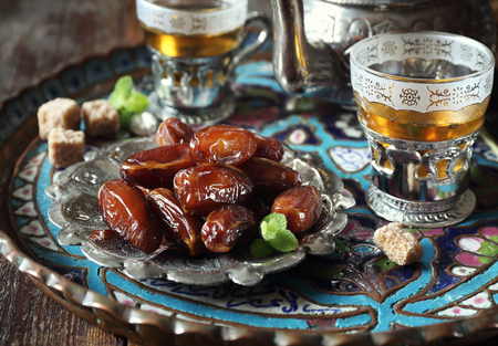 Oriental composition: ripe dates and sweet green tea Stock Photo