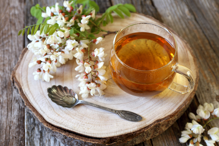 Summer Tea Party: Herbal tea and  flowering acacia on wooden table Stock Photo