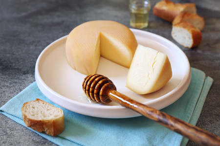 French cheese, baguette and honey on  wooden table