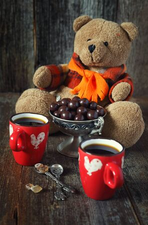 solicitous: Teddy bear, two cups of coffee  and chocolate drops. Toned image