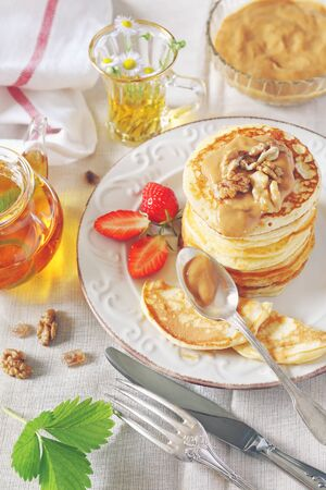 Pancakes with strawberries and herbal tea. Toned image Stock Photo