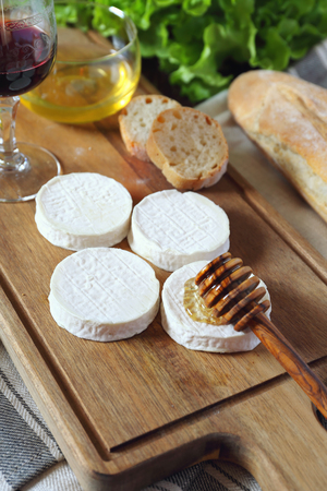 Soft French goat cheese Rocamadour, bread, honey, lettuce and glass of red wine. Focus selective Stock Photo