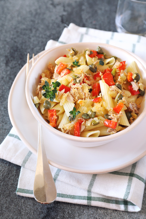 Italian pasta penne with tuna, bell pepper and capers Stock Photo