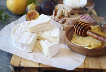 Chesse plate: goat cheese, fruits, mozzarella and bread Stock Photo
