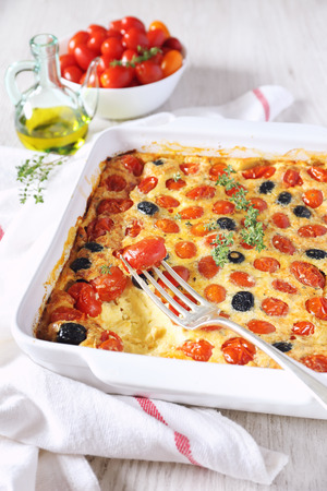 Vegetable Clafoutis with red cherry tomatoes and olives in ceramic bakeware