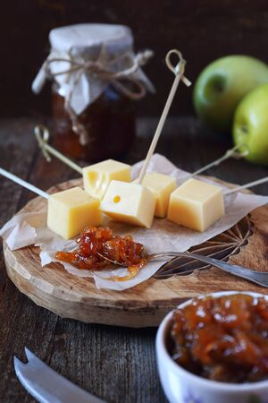 Onion and green apple chutney confiture with solid cheese, rustic style Imagens