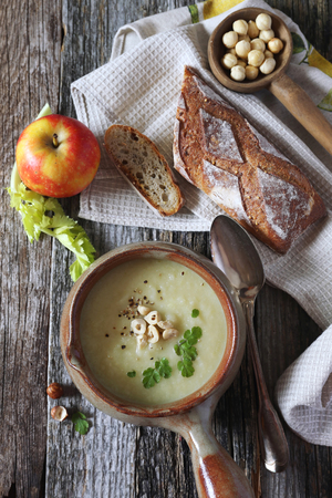Apple celery cream soup with hazelnuts. Top view, rustic style Stock Photo