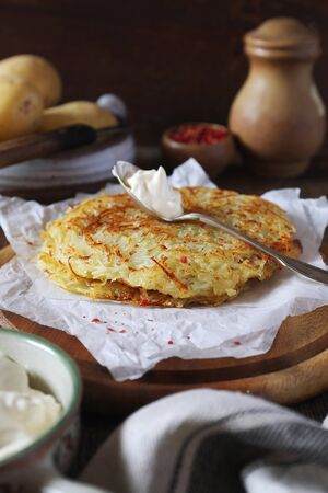 French cuisine. Pomme darphin: roasted pancakes from raw grated potatoes  with sour cream. Rustic style Stock Photo