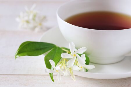 Jasmine tea in a white bone china cup on white background. Focus selective