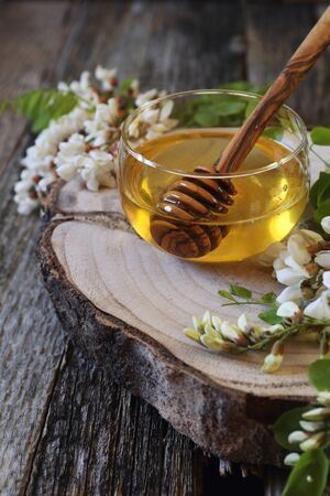 Acacia honey and flowering acacia on wooden table