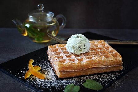 Belgian waffles with Mint Chocolate Chip Ice Cream and mint tea. Focus selective