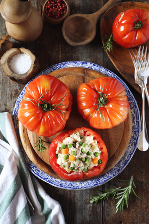 French cuisine:  tuna and vegetables stuffed raw tomatoes bullish heart. Rustic style, top view Фото со стока