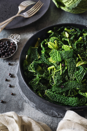 Vegetarian cuisine: fried cabbage with juniper berries. Black background Stock Photo