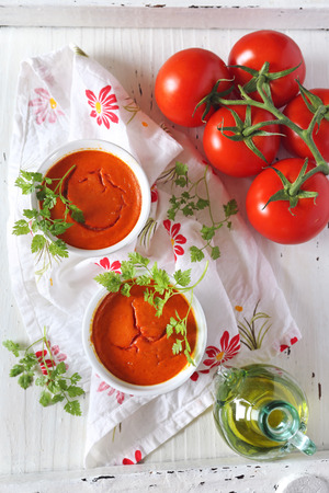 Vegetable appetizer: tomato soufflе on light background, bunch of tomatoes and olive oil, two servings, top view