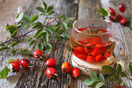 Rosehip tea in glass cup and berries. Focus selective