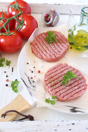 Ground meat steak. Two raw patty on plate, olive oil and bunch of tomatoes Zdjęcie Seryjne