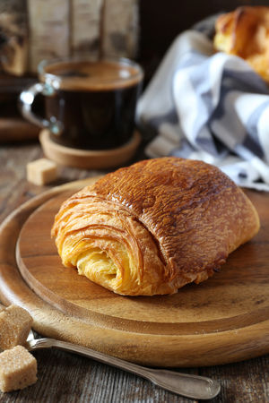 French breakfast: sweet puff pastry bun and cup of coffee. Rustic style 免版税图像