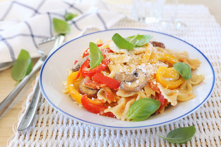 Italian cuisine. Neapolitan pasta. Farfalle with mushrooms and sweet belle pepper, parmesan cheese and basil dressing