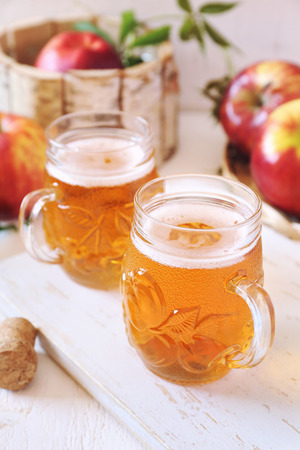 Two cups of Apple Cider and red apples in wooden  basket on light background