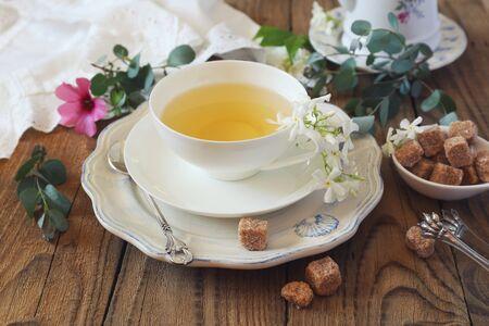 Decorative composition of vintage style: romantic tea drinking with jasmine tea. Toned image
