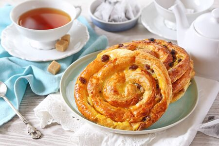 French roll raisin buns, teapot and cup of tea bag on light background