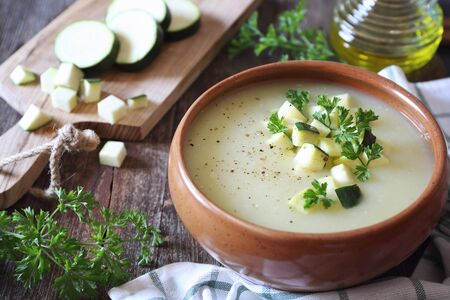 Zucchini vegretable cream soup, parsley dressing on wooden background. Rustic style