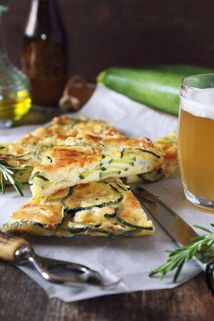 Scarpaccia, Italian cuisine. Slices of thin zucchini pie and mug of light beer Zdjęcie Seryjne