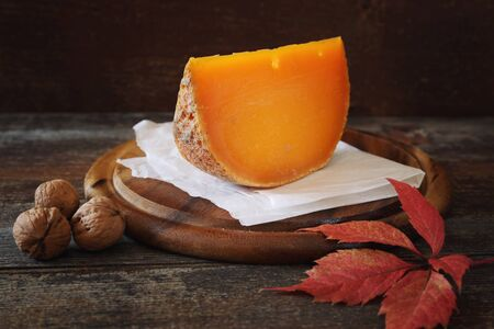 Mimolette cheese and walnuts on a wooden cutting board