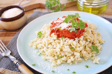 Pearl barley with tomato sauce and grated parmesan cheese, parsley dressing Reklamní fotografie