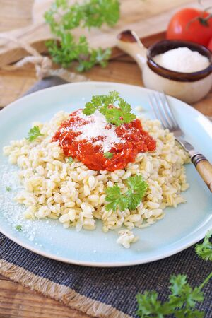 Pearl barley with tomato sauce and grated parmesan cheese, parsley dressing Stock Photo