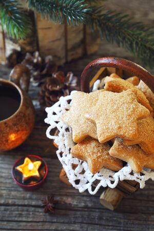 New Year composition with burning candle: cup of coffee and Christmas cinnamon cookies on wooden background