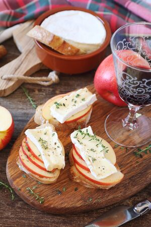 Apples and Camembert cheese bread toast and glass of red wine. Healthy savory sandwich on wooden cutting board