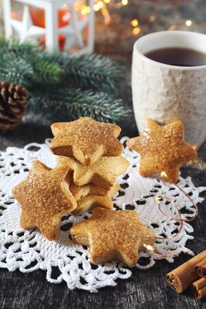 Christmas cinnamon cookies (spice-cake),  cup of tea and New Years decoration. Rustic style