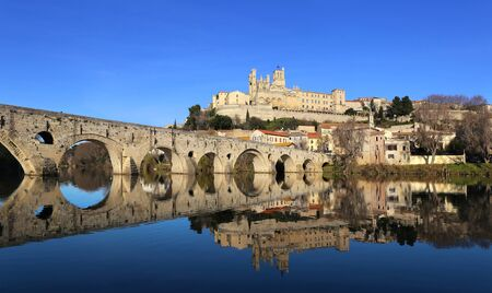 Landscapes of southern France. Winter Beziers city, Occitanie region. Ancient bridge and cathedral, reflection