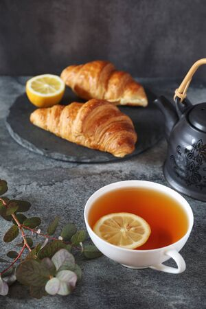 Lemon tea, two fresh croissants and teapot on dark background Banco de Imagens