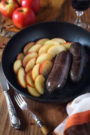 Traditional French cuisine: fried blood sausage and apples