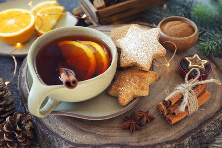 Christmas cinnamon cookies (spice-cake),  cup of spicy tea and New Years decoration. Rustic style, toned image
