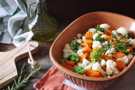 Stewed vegetables (carrots, cauliflower, broccoli) in ceramic bakeware and olive oil, rustic style Stock Photo