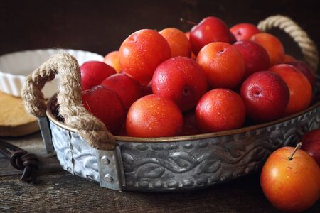 A lot of red plums in basket on wooden background Stock Photo