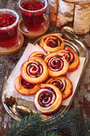 Festive winter pastries.  Sweet cranberry roll buns with chocolate drops and two cups of cranberry fruit drink. Focus selective Imagens