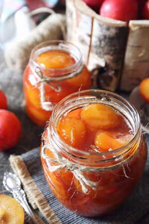 Autumn sweet. Homemade red plums jam in two jars and fruits. Rustic style Stock Photo
