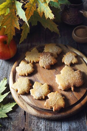 Autumn coffee break: cinnamon cookies in form of maple leaves, cup of coffee and yellow leaves. Toned image Stock Photo - 133058151