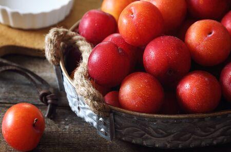A lot of red plums in basket on wooden background. Rustic style