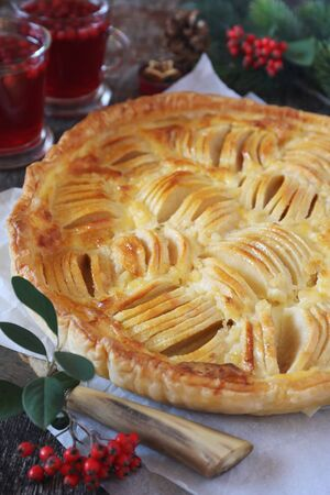 New Year dessert: apple tart and two cups of cranberry fruit beverage Stock Photo - 133058136