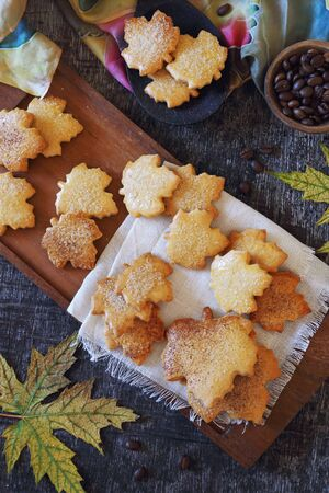 Autumn coffee break: cinnamon cookies in form of maple leaves, coffee beans and yellow leaves. Toned image, top view Stock Photo - 133058298