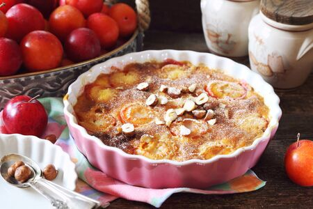 Autumn dessert. Red plums clafoutis, hazelnut and icing sugar dressing, french cuisine on wooden background