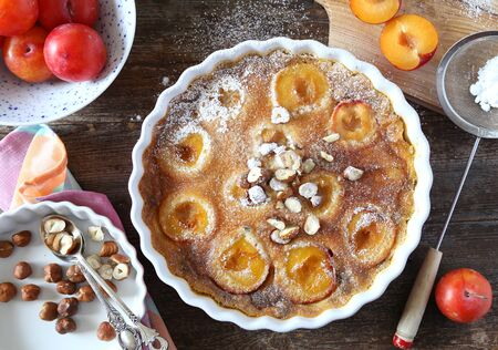 Autumn dessert. Red plums clafoutis, hazelnut and icing sugar dressing, french cuisine on wooden background. Top view