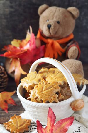 Autumn composition: cinnamon cookies in form of maple leaves, red leaves and Teddy bear on wooden background