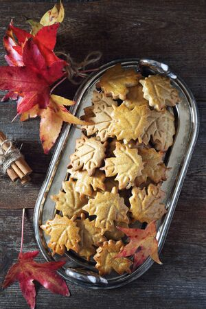 Autumn composition: cinnamon cookies in form of maple leaves and red leaves on wooden background. Top view