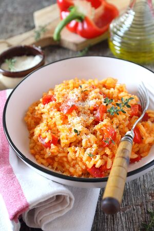 Italian food. Plate of red bell pepper risotto, olive oil and parmesan cheese on wooden background